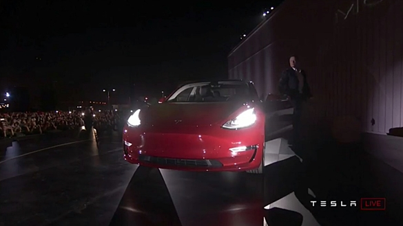 Tesla CEO Elon Musk exits from a Model 3 on stage.